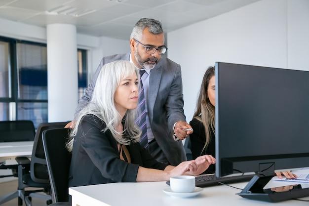 Босс смотрит и указывает на монитор, комментирует проект, пока менеджер печатает и работает над презентацией. средний план. концепция делового общения