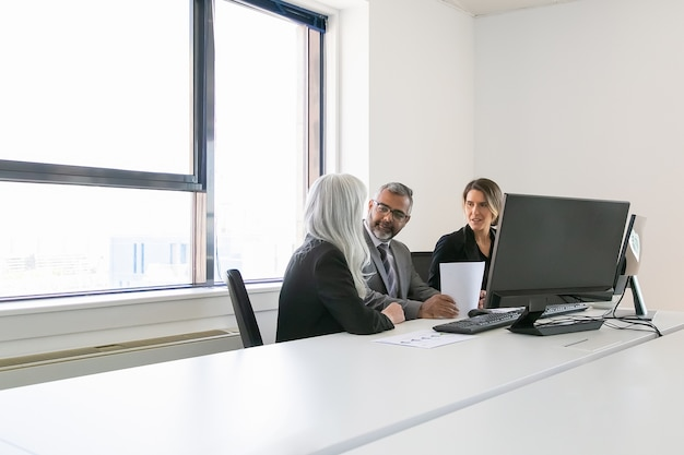 Boss and managers analyzing reports and discussing work. team sitting together at workplace with monitors, papers and talking. copy space. business meeting concept