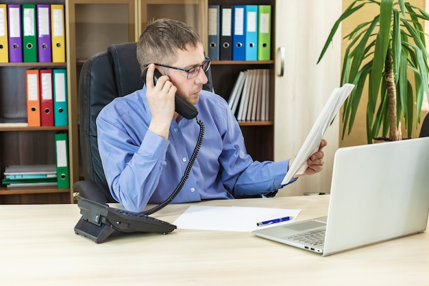 The boss in the office at his desk talking on the phone holding a financial report in his hands