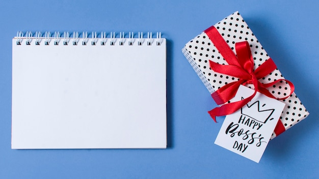 Boss's day arrangement on blue background with empty notepad