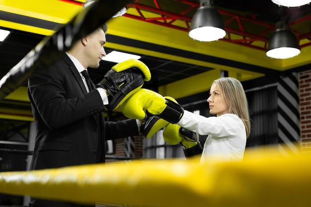 Босс тренирует своего сотрудника в боксерских перчатках на ринге