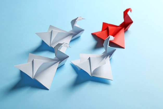 ボス対リーダーの概念。青い背景の上の赤いものの後ろに白い折り紙の鳥