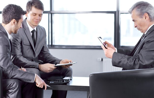 コピースペースのあるオフィスの写真に座っているクリップボードを持つ上司
