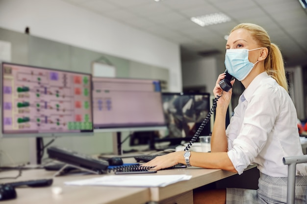 Boss with mask on sitting in control room in heating plant and having conversation during coronavirus.