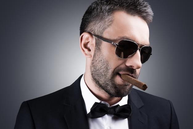 偉そうな自信。葉巻を吸って灰色の背景に立っている間目をそらしている正装とサングラスのハンサムな成熟した男の肖像画