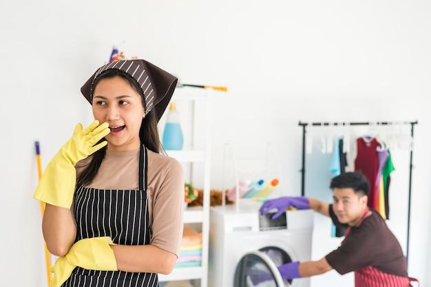 Властная домохозяйка смеется над мужем для стирки, пока он расстроен и смотрит на нее