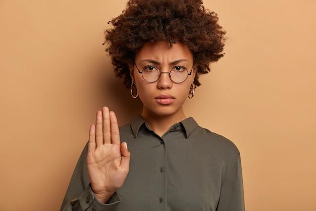 偉そうな真面目な女性はカメラを厳しく見て、手のひらを伸ばし、タブーや禁止を表現し、顔を眉をひそめる