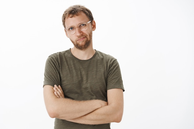 Bossy smart and creative displeased businessman in dark-green t-shirt and glasses tilting head and smirking from dissatisfaction crossing hands on chest disliking new concept