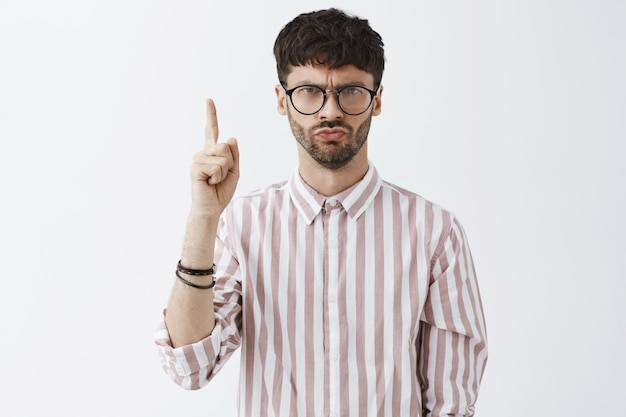 Bossy stylish bearded guy posing against the white wall with glasses