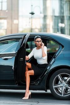 거만한 여자. 그녀의 차에서 나오는 동안 휴대 전화로 얘기하는 자신감이 젊은 사업가