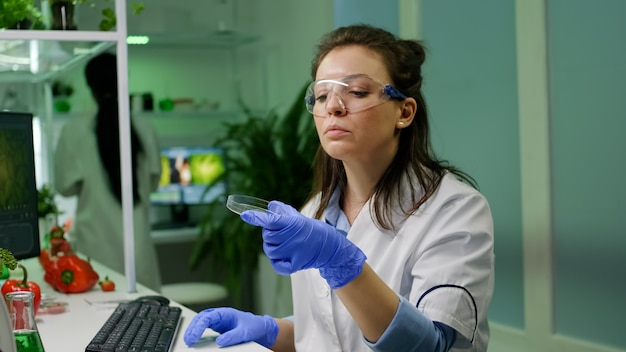 Botanist woman looking at petri dish with leaf sample checking gmo test typing scientist researcher