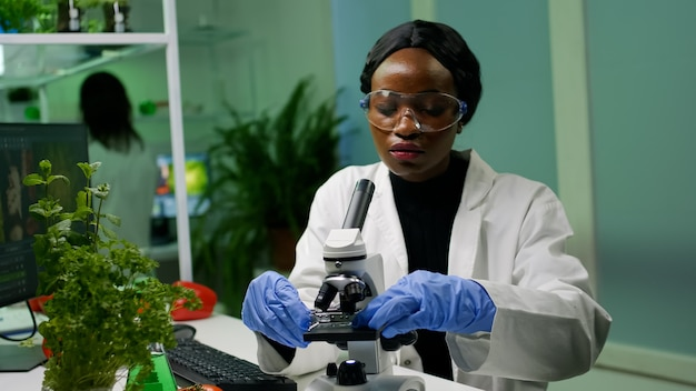 Botanist woman looking at test sample under microscope observing genetic mutation on plants