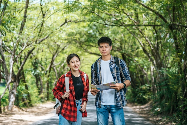 Туристы мужского и женского пола стоят, чтобы увидеть карту на дороге.