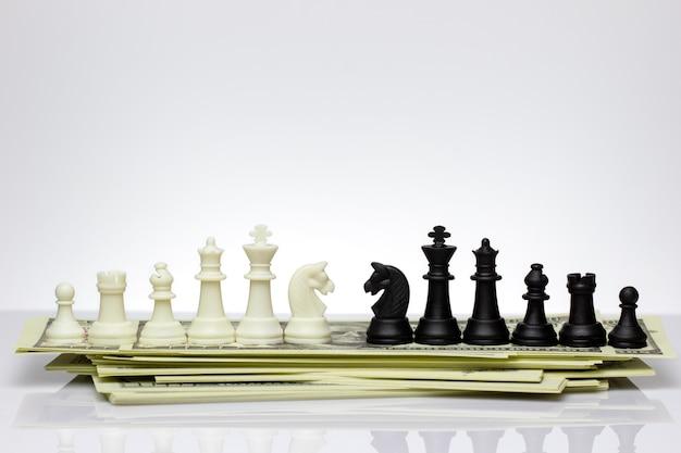 Белые и черные шахматы стоят лицом друг к другу на долларовой банкноте.