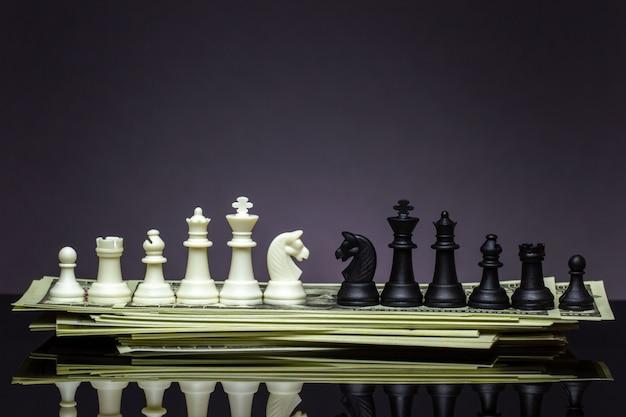 Белые и черные шахматы смотрят друг на друга на долларовой банкноте