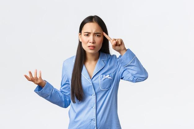 誰かが愚かで狂ったように振る舞い、青いパジャマを着て、イライラして手を上げ、こめかみの上で指を転がして、誰かを叱る、悩んで混乱しているアジアの女の子