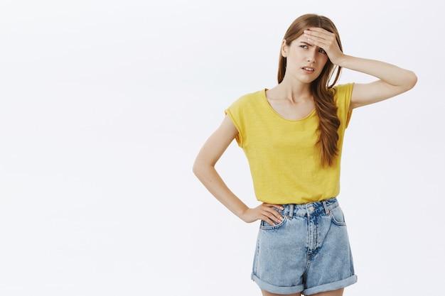 Обеспокоенная и уставшая девушка, держащая руку на лбу, обеспокоена, чувствует себя расстроенной или разочарованной
