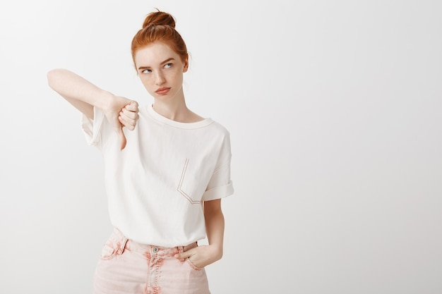 Bothered and annoyed redhead girl showi thumb-down and roll eyes unimpressed