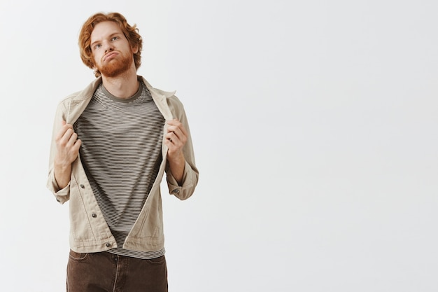 Bothered bearded redhead guy posing against the white wall