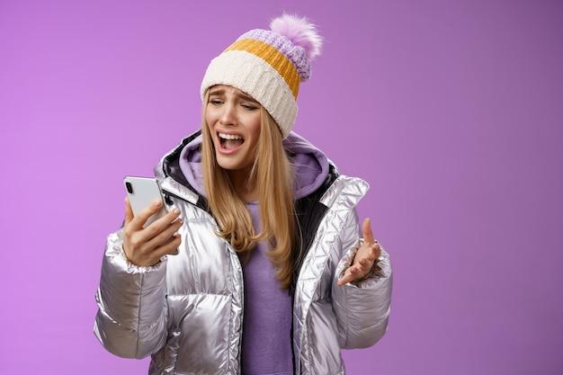 不満を訴えるかわいいブロンドの女の子が愚かなスマートフォンを叫んで不幸に立っている不幸な録音オーディオメッセージを叫んで携帯電話を動揺させ、紫色の背景を立っている。技術コンセプト