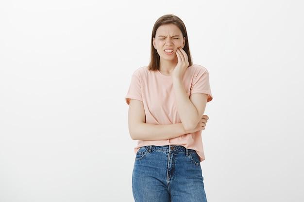 Обеспокоенная милая женщина гримасничает от боли и трогает щеку, жалуется на зубную боль, нужен стоматолог