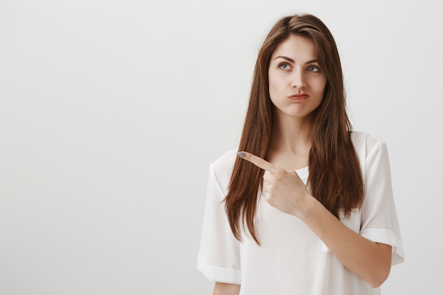 Bothered and disappointed woman pouting with regret as pointing upper left corner