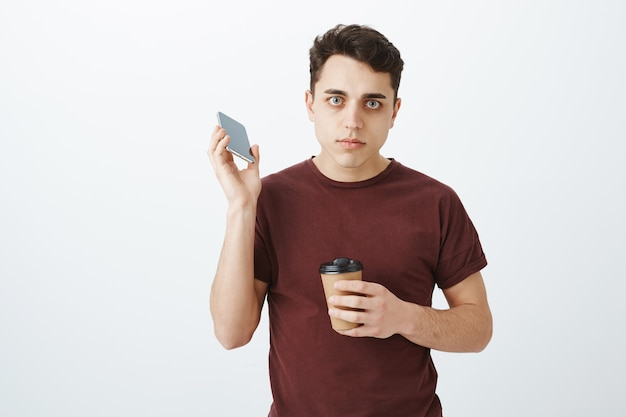 Uomo attraente stufo infastidito in maglietta rossa che parla dal telefono