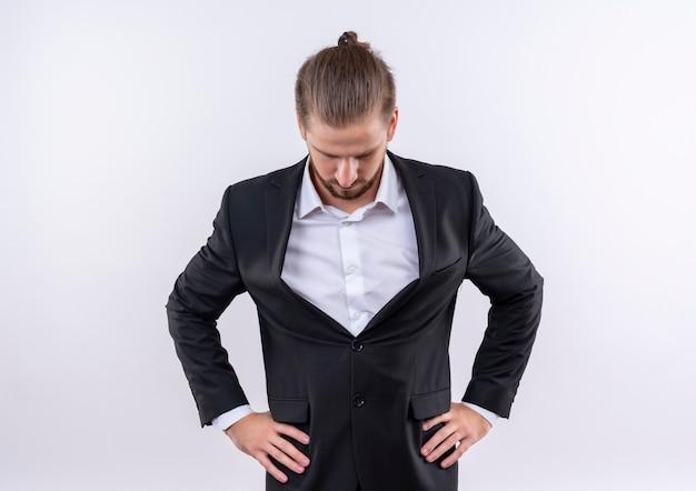 白い背景の上に立って見下ろしているスーツを着ているハンサムなビジネスマンを悩ませた