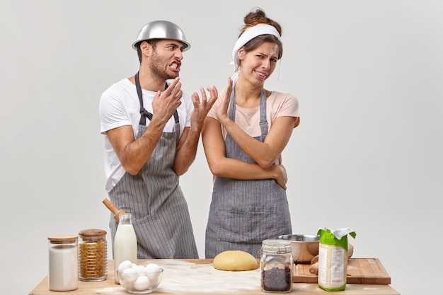 Bothered housewife doesnt want to listen annoyed husband, cook dinner together, stand irritated and tired, use healthy products, make dough, isolated on white wall. culinary, food and people