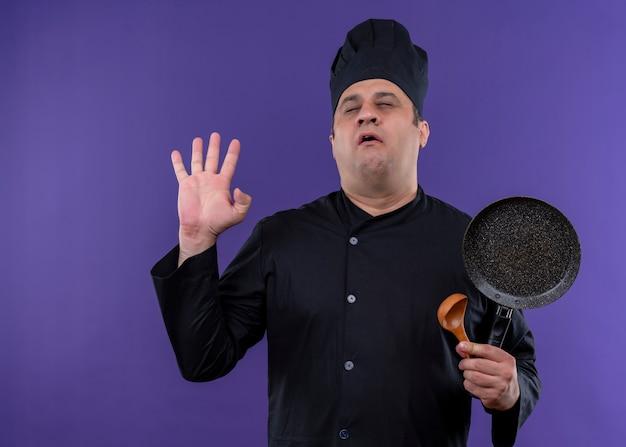 黒のユニフォームを着て、紫色の背景の上に立っている目を閉じてフライパンを保持している帽子を調理する気になる男性シェフ