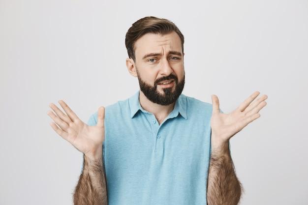 Обеспокоенный мужчина поднимает руки вверх и неохотно гримасничает