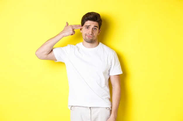 Bothered man shooting himself with finger gun, looking displeased and tired, standing against yellow background.