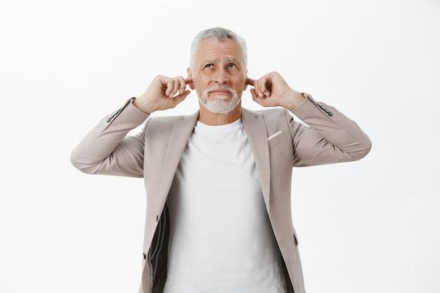 귀찮은 노인 사업가 손가락으로 귀를 닫고 위층에서 시끄러운 음악을 불평
