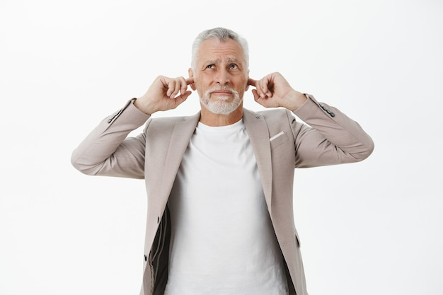Bothered old businessman shut ears with fingers and complaining loud music upstairs