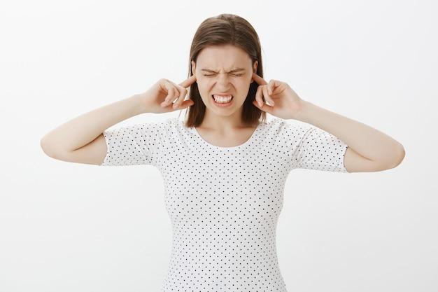 Donna adolescente infastidita che non ama il suono fastidioso, orecchie chiuse con le dita infastidite