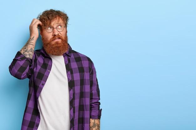 Обеспокоенный задумчивый бородатый мужчина с вьющимися рыжими волосами, чешет затылок, что-то думает