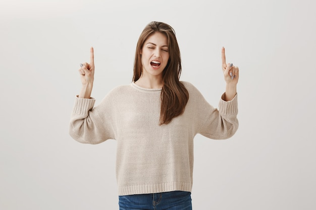 Bothered woman expressing regret as pointing fingers up and sighing disappointed