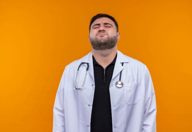 Il giovane medico maschio barbuto infastidito indossa camice bianco con lo stetoscopio che sembra stanco e ha sottolineato gli occhi di chiusura