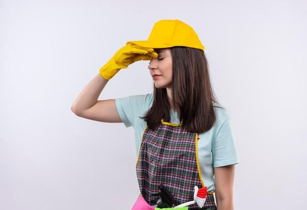 Giovane bella ragazza infastidita che indossa grembiule, berretto e guanti di gomma chiudendo il naso tra gli occhi chiusi