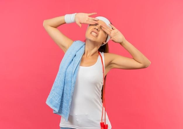 분홍색 벽 위에 서있는 짜증이 나는 표정으로 손바닥으로 눈을 감고 그녀의 어깨에 머리띠와 수건으로 운동복에 젊은 피트니스 소녀를 괴롭 혔습니다.
