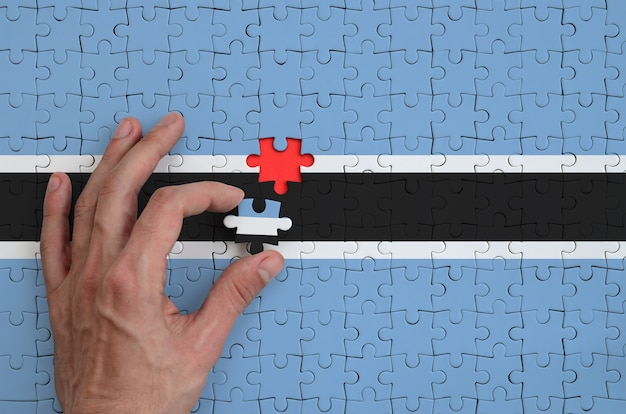 Botswana flag  is depicted on a puzzle, which the man's hand completes to fold