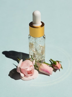 Bottle of 24k gold serum on a blue background with rose flowers. the concept of skin care at home.