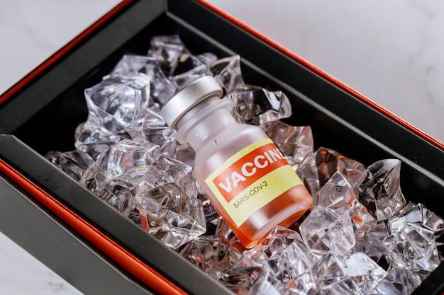 Covid-19コロナウイルスsars-cov-2ワクチンの滅菌バイアルを氷上で瓶詰めし、ワクチンを低温に保ちます。