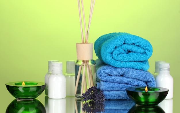 Bottle of air freshener, lavander and towels on green
