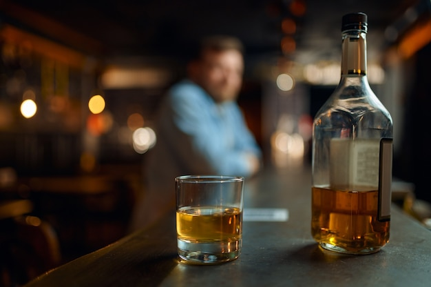 Bottle of alcohol and glass on counter in bar, male person on dlur background. man resting in pub, human emotions and leisure activities, stress relief concept