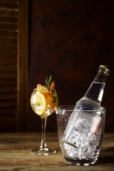Бутылка и стакан спирта со льдом и апельсином на темном деревянном фоне