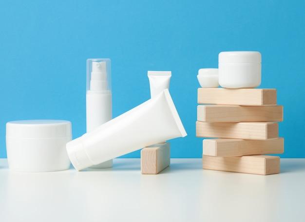 白い背景の上の化粧品のためのボトルと空の白いプラスチックチューブ。クリーム、ジェル、美容液、広告、製品プロモーションのパッケージ、モックアップ