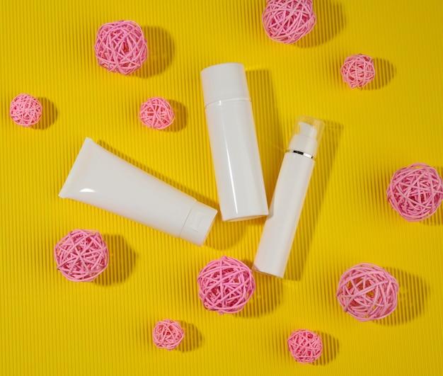 Бутылка и пустые белые пластиковые тубы для косметики на желтом фоне. упаковка для крема, геля, сыворотки, рекламы и продвижения продукции, вид сверху