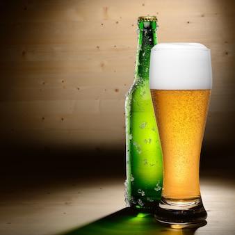 コピースペースと木の背景にビールのボトルとグラス