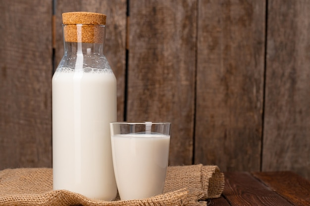 병 및 나무 테이블에 우유의 유리를 닫습니다.